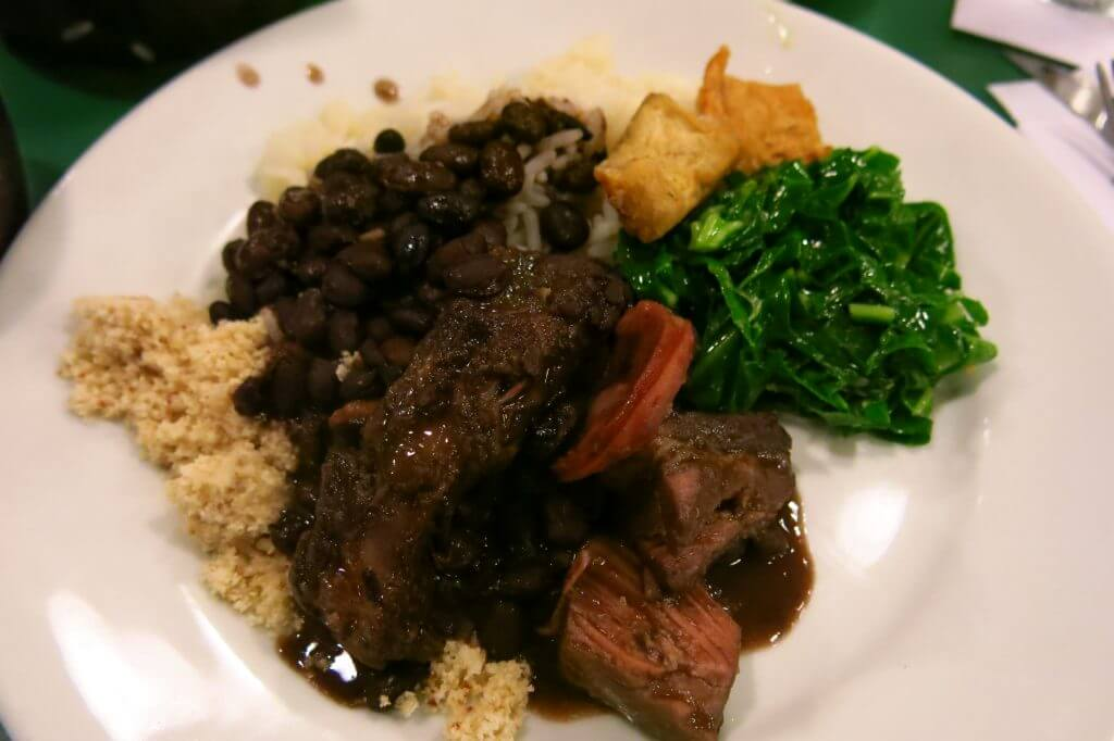 A plate of Brazilian food, feijoada