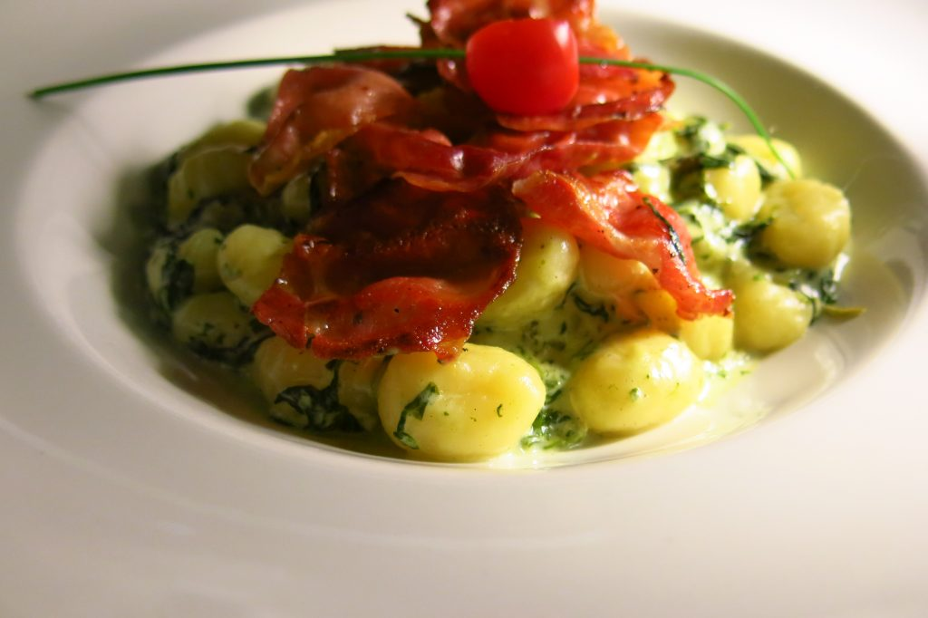Housemade gnocchi with ham strips and creamy spinach