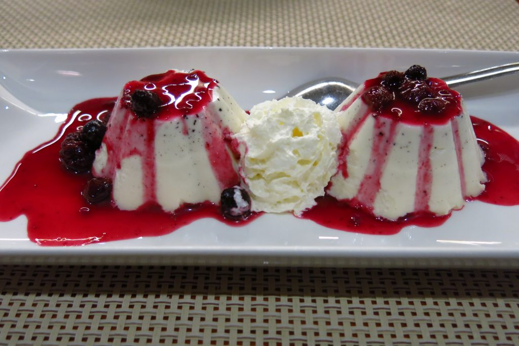 Panna Cotta served with berries and whipped cream in the middle
