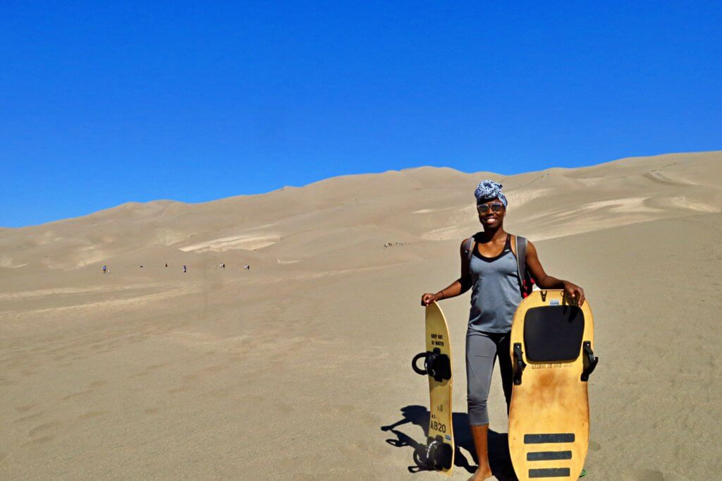 Holding a sandboard and sand sled (Colorado)